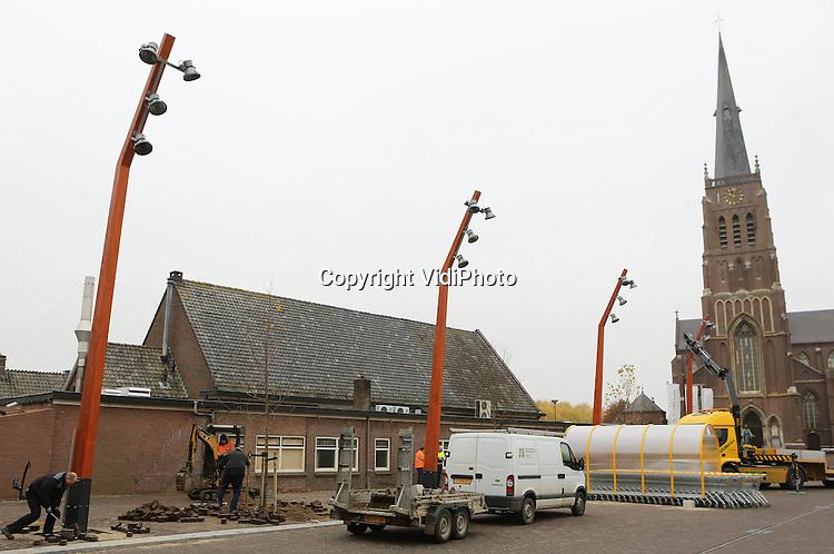 Foto: VidiPhoto..DREUMEL - In het centrum van Dreumel in Gelderland zijn vrijdag de eerste vier lichtmasten in Nederland van accoya geplaatst. Accoya is hout van naaldbomen met azijnzuur verduurzaamt, een Nederlandse vinding. De lichtmasten hebben hierdoor een levensduur van zeker 50 jaar. Normale straatverlichting gaat ongeveer 15 jaar mee. De lichtmasten met vier lampen, die ook voor evenementen gebruikt kunnen worden, hebben meer sfeer en een warmere uitstraling dan normale straatverlichting. Uitvoerder van het project is Postma GWW uit Bergharen. Benelux Lighting uit sneek is de bedenker van de mast. Houtindustrie Buitenpost BV heeft de lichmasten gemaakt..