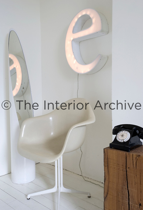 "An Eames chair stands in the corner of the room overlooked by a large ""e"" wall light and flanked by a mirror and a telephone on a wooden pedestal"