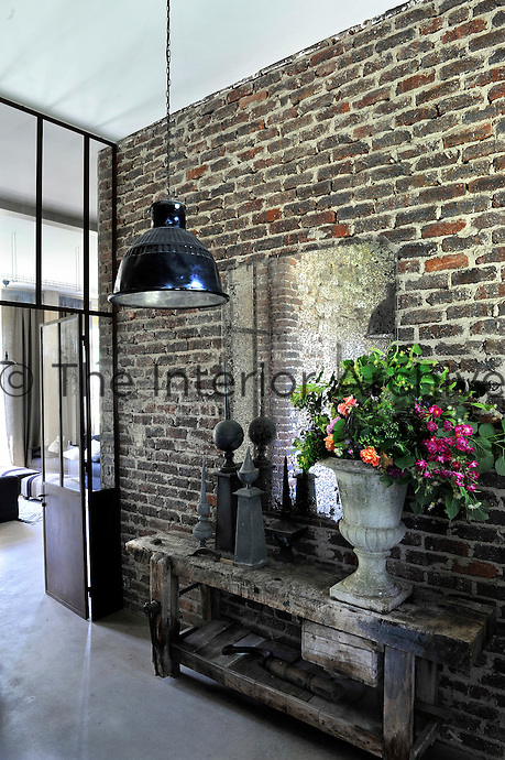 An original brick wall in the corridor has been left unrestored and an old wooden workbench is used as a console table