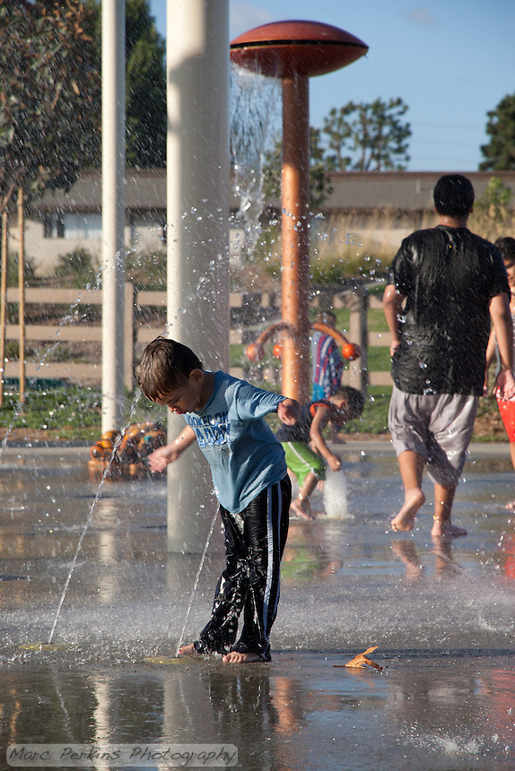 A boy in a blue shirt looks down at water spraying up at him in the splash pad at Stanton Central Park.