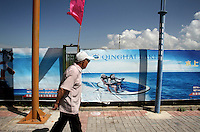 A man walks past an advertisement for jet-skiing. Qinghai Lake, China's largest inland body of water lies at over 3000m on the Qinghai-Tibetan Plateau. The lake has been shrinking in recent decades, as a result of increased water-usage for local agriculture. Qinghai Province. China. 2010