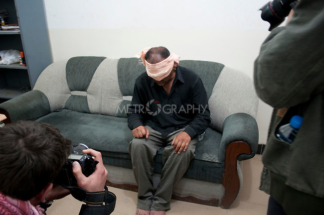 KIRKUK, IRAQ:  Press photographers take pictures of an Arab man from the Hai Askari neighborhood of Kirkuk while he awaits interrogation on the eve of the Iraqi Parliamentary Elections.  The man is suspected of planting a roadside bomb on March 4th that wounded 6 people.