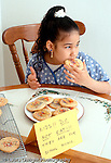 7 year old girl sitting at table  eating forbidden cookie Hispanic Dominican vertical
