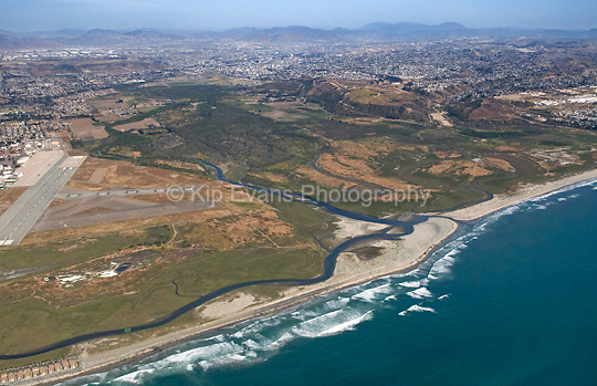 Aerial view of the Tijuana River National Estuarine Research Reserve and the mouth of the Tijuana River breaking over a sandbar and entering the Pacific Ocean. Looking southeast, the U.S./Mexico Border and the city of Tijuana can also be seen in the background.