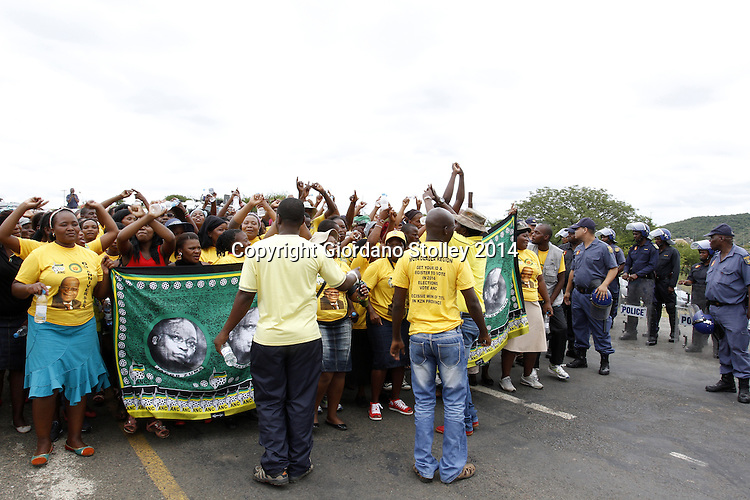 DURBAN - 11 January 2014 - African National Congress supporters march past a house that EFF leader Julius Malema was due to hand over to a grandmother looking after four children. Police to the right ensure that they do not gain access to the property where EFF party members were putting the last touches to the house. Picture: Allied Picture Press/APP