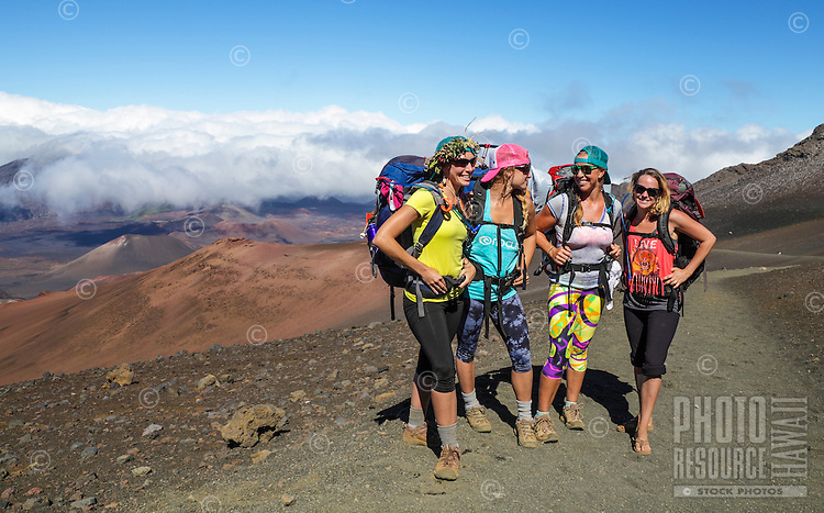 Four backpackers pause on the Sliding Sands Trail in Haleakala National Park, Maui.