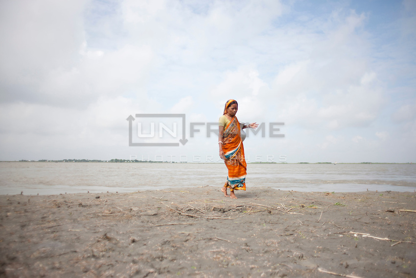 A woman collets drinking water from the river. The river became the main source of water in these days for the affected people. As a result people affected by diseases.  Every year in Bangladesh, millions of people are affected by river erosion that destroys home, farmland, communication infrastructure. In the last couple of days erosion by the Padma River has caused extensive damages to houses, agricultural lands, roads etc. In Dohar, lots of people lost their lands and homes due to Padma river banks erosion. Dohar, Dhaka, Bangladesh.