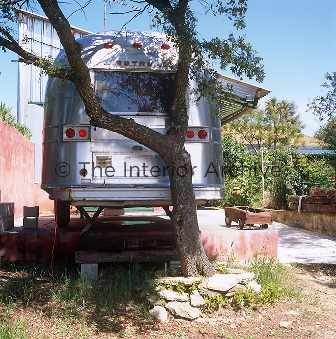 A vintage steel Airstream trailer in a garden.