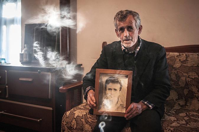 Vater von Thoma Andoni mit dem Foto von Thoma,der bei Elektrifizierungsarbeiten ums Leben gekommen ist. Gjinar, Shpati 2013, Strom wird  in Albanien hauptsächlich aus Wasserkraft gewonnen. Zu kommunistischen Zeiten wurde das Land elektrifiziert. Die Infrastruktur kann aber mit dem hohen Verbrauch heutzutage nicht mithalten