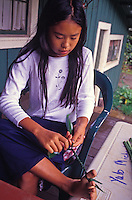 At Kokee Museum on Kauai, a girl twists ti leaves into a lei.  The museum showcases exhibits on science and culture, gives craft demonstrations, and has a gift shop