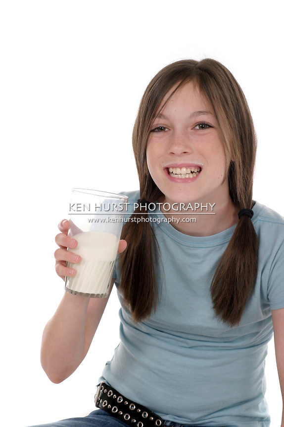 Little girl with pig tails in her hair drinking a big glass of cold milk.  Shot isolated on white.