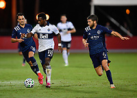LAKE BUENA VISTA, FL - JULY 26: Cristian Dájome of Vancouver Whitecaps FC dribbles away from Luis Martins of Sporting KC and Ilie Sánchez of Sporting KC during a game between Vancouver Whitecaps and Sporting Kansas City at ESPN Wide World of Sports on July 26, 2020 in Lake Buena Vista, Florida.