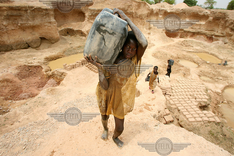 A young boy collects water from a brick making well.