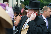 A man in a top hap speaks on a mobile phone outside a pub in Ascot.