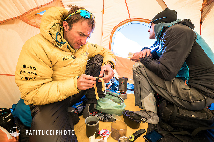 Ueli Steck and David Göttler inside their advance basecamp tent during a climbing expedition to the 8000 meter peak Shishapangma, Tibet. Ueli is checking his watch.
