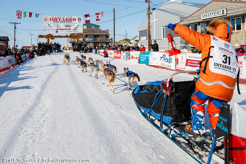 Last place finisher and Red Lantern Award winner Cindy Abbott holds up the red lantern as she runs down the finish chute in Nome during the 2017 Iditarod on Saturday March 18, 2017.<br /> <br /> Photo by Jeff Schultz/SchultzPhoto.com  (C) 2017  ALL RIGHTS RESERVED