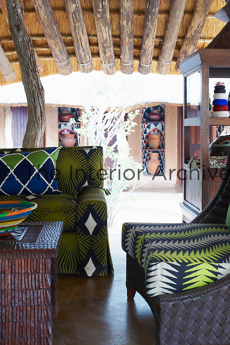 Seating with green patterned upholstery in a sitting area at the Singita Pamushana Lodge, Malilongwe Trust, Zimbabwe