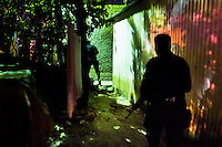 Policemen from the special emergency unit (Halcones) chase supposed gang members during the night in a gang neighbourhood of San Salvador, El Salvador, 15 December 2013. Although the murder rate in the country has dropped significantly, after a truce between two major street gangs (Mara Salvatrucha and Barrio 18) was agreed in 2012, the lack of security and violence are still the main issues in people's daily life. Due to the fact the gangs have never stopped their criminal activities (extortions, distribution of drugs and kidnappings), the Police anti-gang forces keep running their operations and chasing the 'homeboys' (how the gang's foot soldiers usually call themselves) in the poor, socially deprived suburbs of Salvadoran cities.