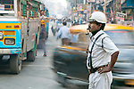 An officer stands in a busy intersection, Kolkata, India