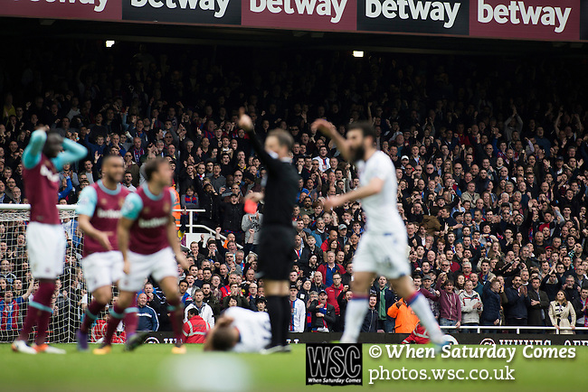 West Ham United 2 Crystal Palace 2, 02/04/2016. Boleyn Ground, Premier League. Visiting fans watching as referee Mark Clattenburg sends off home midfielder Cheikhou Kouyate during the second-half at the Boleyn Ground as West Ham United hosted Crystal Palace in a Barclays Premier League match. The Boleyn Ground at Upton Park was the club's home ground from 1904 until the end of the 2015-16 season when they moved into the Olympic Stadium, built for the 2012 London games, at nearby Stratford. The match ended in a 2-2 draw, watched by a near-capacity crowd of 34,857. Photo by Colin McPherson.