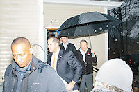 Carrying an umbrella, Ohio governor and Republican presidential candidate John Kasich returns to his campaign bus after a town hall campaign event at Raymond VFW Post 4479 in Raymond, New Hampshire, on Wed., Feb. 3, 2016.