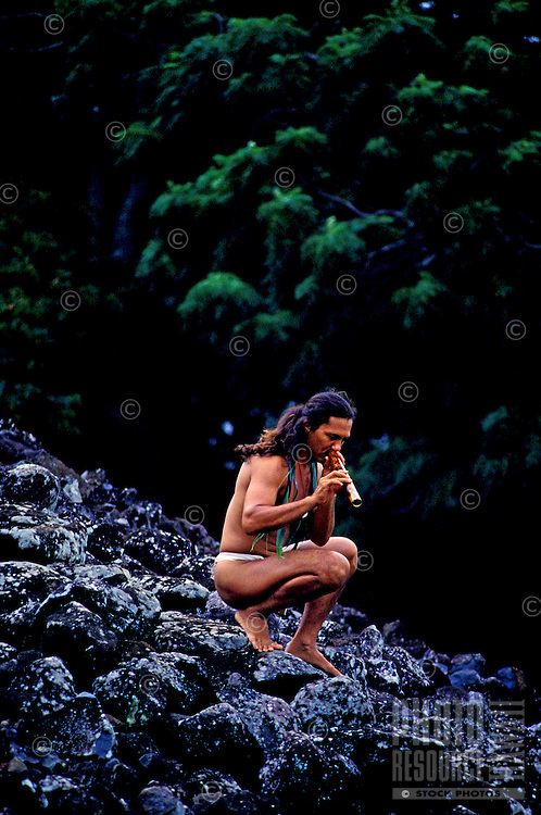 A local man wearing a loin cloth playing a bamboo nose flute beside Ulupo Heiau near Kailua on the windward side of Oahu.