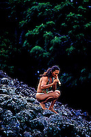 A local man wearing a loin cloth playing a bamboo nose flute beside Ulupo Heiau near Kailua on the windward side of Oahu.