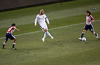 LA Galaxy midfielder and Captain David Beckham (23) passes a ball between Chivas USA players defender Jonathan Bornstein (13-L) and midfielder Francisco Mendoza (6-R) during the Super Clasico MLS match. The LA Galaxy defeated Chivas USA 5-2 during the SuperClasico at the Home Depot Center Stadium, in Carson, California, Saturday, April 26, 2008.