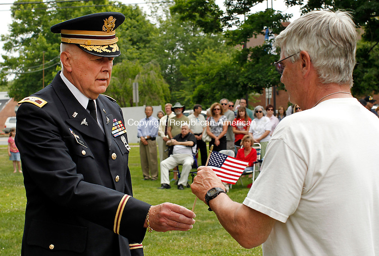 """Cheshire, CT-29, May 2010-052910CM01 Colonel Kenneth Gertz, (Ret. Army) passes a flag to Ford Cole, (Ret. Navy) during a ceremony called """"Field of Flags."""" The event was held honoring fallen soldiers in the Iraq and Afghanistan.  Some 5,487 flags were seen on the green in front of the First Congregational Church in Cheshire.  The flag passed above was in memory of Staff Sergeant Michael Rivera (CT National Guard Unit 102), who was killed in action. --Christopher Massa Republican-American"""