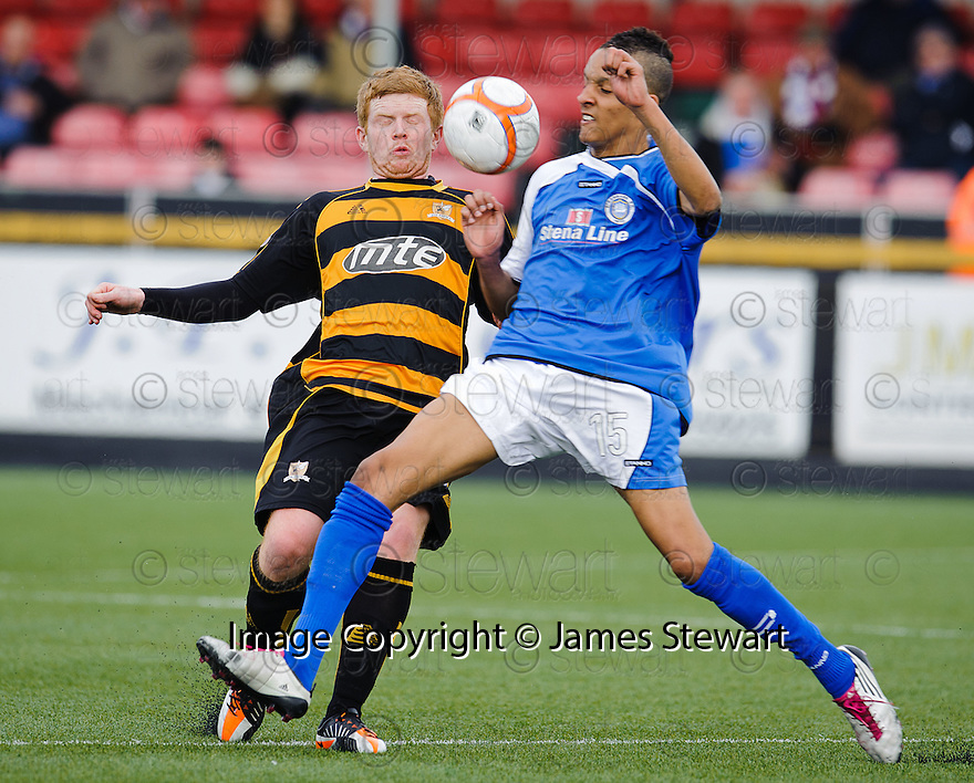 Alloa's Ryan McCord and Stranraer's Zakaria Belkouche challenge for the ball.