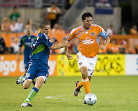 Seattle Sounders midfielder Osvaldo Alonso (6) grabs hold of Houston Dynamo forward Brian Ching (25).  Houston Dynamo tied Seattle Sounders 1-1 on August 23, 2009 at Robertson Stadium in Houston, TX.