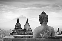 A Buddha statue in Borobudur, Indonesia, peers in the distance at Mount Merapi.
