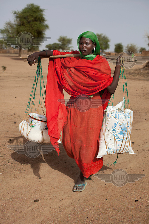 A woman carries sacks of food aid that she has just collected from an Oxfam distribution point. Across the Sahel drought, exacerbated by a rise in global food prices, has left about 40% of Niger's population facing severe food insecurity. This particularly affects women and children with an estimated 127,000 children under five years old predicted to suffer from severe malnutrition during 2012.