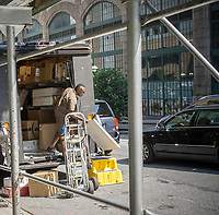 A UPS worker with his truck and deliveries in New York on Wednesday, June 28, 2017. United Parcel Service announced that it will freeze the pension program for its nonunion workers. The freeze will affect 70,000 employees taking place in five years and will be replaced with 401K accounts. (©Richard B. Levine)