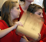 Photo by Phil Grout..The heat wave is on, right in the middle of North Carroll's graduation,.so school chorus member Amy Malinowski uses a cardboard box.to fan herself and her friend Molly Davidson.