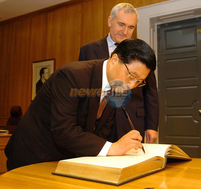 Dublin Ireland, Irish Prime Minister Bertie Ahern TD (B) welcomes the Vice-Premier of the State Council of the PeopleÕs Republic of China, H.E. Mr Huang Ju to Dublin 15/11/04. Vice Premier Huang signs the Governments visitors book before his private meeting with the Irish Prime Minister..Photo: AFP Photo Fran Caffrey/Newsfile...This Picture has been sent to you by Newsfile Ltd..The Studio,.Millmount Abbey,.Drogheda,.Co. Meath,.Ireland..Tel: +353(0)41-9871240.Fax: +353(0)41-9871260.ISDN: +353(0)41-9871010.www.newsfile.ie..general email: pictures@newsfile.ie