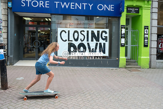 A young girl skateboarding past a shop that is closing down in Newquay, Cornwall.