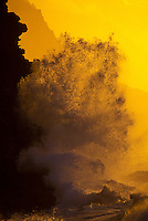 Kee sunset with wave crashing against cliffs