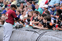 First baseman Dominic Smith (22) of the Savannah Sand Gnats signs autographs before a game against the Greenville Drive on Thursday, June 19, 2014, at Fluor Field at the West End in Greenville, South Carolina. Smith, a first-round pick by the New York Mets in the 2013 First-Year Player Draft, is the Mets' No. 4 prospect, according to Baseball America. Savannah won, 6-3. (Tom Priddy/Four Seam Images)
