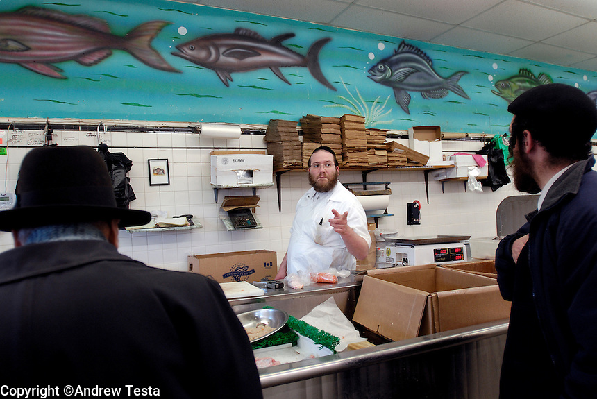 USA. Brooklyn. 2006..Zalmen Teitelbaum serves fish at the Mehadron Fish Market inc, Borough Park, Brooklyn..©Andrew Testa