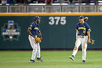 Michigan Wolverines outfielders Christian Bullock (5) and Jordan Brewer (22) celebrate beating the Florida State Seminoles in the NCAA College World Series on June 17, 2019 at TD Ameritrade Park in Omaha, Nebraska. Michigan defeated Florida State 2-0. (Andrew Woolley/Four Seam Images)