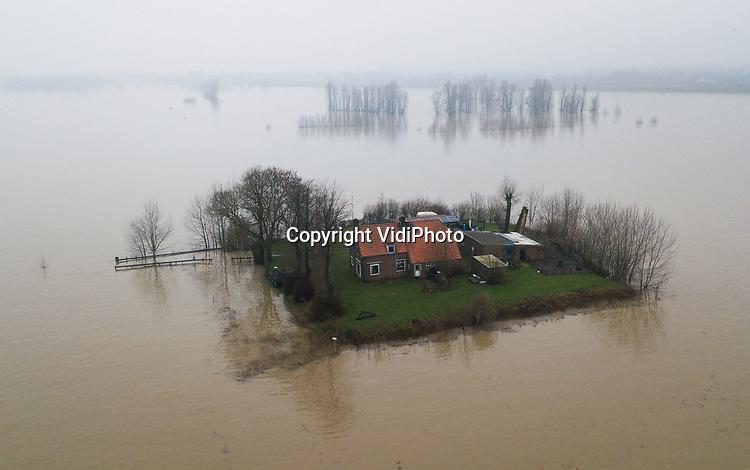 Foto: VidiPhoto<br /> <br /> OCHTEN &ndash; Steeds meer mensen leven op een eiland. Althans op dit moment en specifiek in de uiterwaarden langs de grote rivieren. Bereikte de Rijn bij Lobith woensdag de voorlopig hoogste waterstand van dit jaar, stroomafwaarts gebeurde dat donderdag pas. Deze woning aan het eind van de Oude Veerweg in Ochten langs de Waal, is vooralsnog onbereikbaar met de auto. De komende dagen blijft de waterstand dalen, met als gevolg dat de waterschappen het druk krijgen met het verwijderen van aangespoeld hout en afval langs de dijken.
