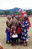 Lolgorian, Kenya. White man wearing a shukka showing something to a group of Maasai girls, one carrying a radio.