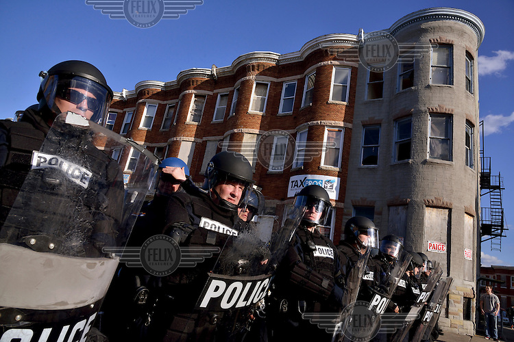 Policemen stand lined up on a suburban street in Baltimore during a protest. <br /> After the violent riots and looting following the funeral of Freddie Gray who died after being arrested in Baltimore, people demonstrate against the excessive use of force by the local police force. <br /> Gray (25) was arrested in 12 April 2015 and died of spinal injuries a week after his arrest which was recorded on a mobile phone by a bystander.