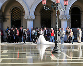 A bride and groom pose for wedding photos in flooded St. Mark's Square in Venice, Italy in the morning of Thursday, October 21, 2010.  The morning is Venice is some of the earliest in memory..Credit: Ron Sachs / CNP