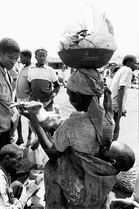 Burundi. Karuzi Province. Kamahro. People from all over the region come every saturday to the outdoor market. A mother carries her sleeping child on the back and a wicker basket on her head. She buys a rabbit which she will later cook and eat with her family. © 2000 Didier Ruef