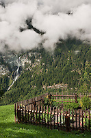 The vegetable garden is enclosed by a rustic palisade and overlooks a spectacular waterfall tumbling down the mountainside