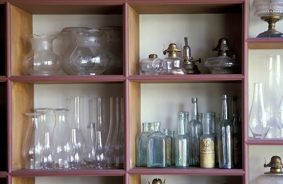 Glass bottles, oil lamps, and tallows on shelves, Sherbrooke Village, Nova Scotia, Canada