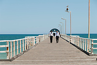 Two young men in business clothes stroll along Henley Jetty at lunchtime on a summer's day, Adelaide, South Australia.