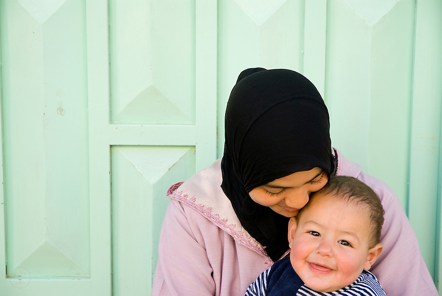 A young Moroccan woman holds a plump, happy baby in Sefrou, Morocco.